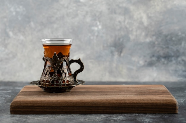 A glass cup of hot tea on a wooden cutting board .