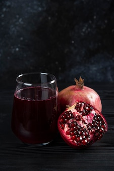 A glass cup of juice with pomegranate on dark.