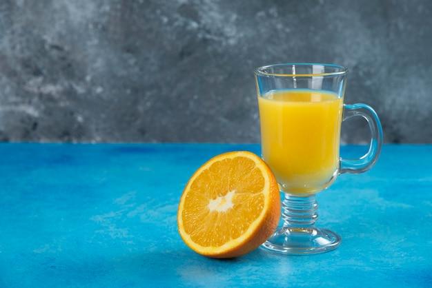 Una tazza di vetro di succo con fetta d'arancia.