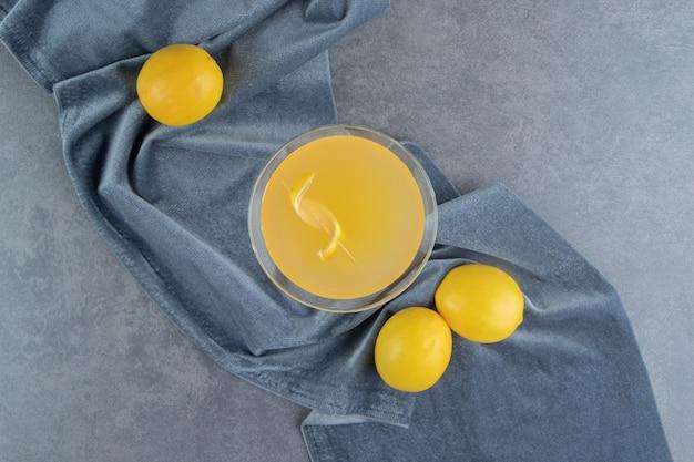Una tazza di vetro di limonata con limoni interi