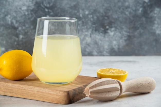 Una tazza di vetro di limonata e alesatore di legno.