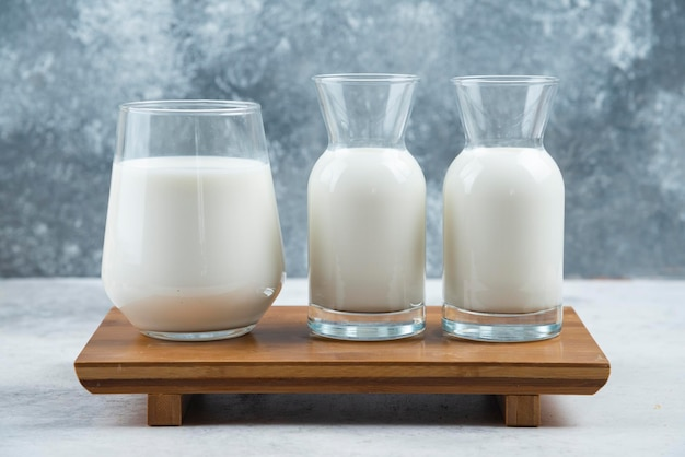 A glass cup of milk and two glasses jar of milk on a wooden small desk.