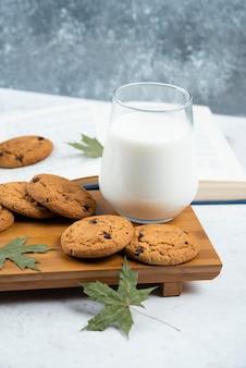 Una tazza di latte con biscotti al cioccolato su un tagliere di legno.