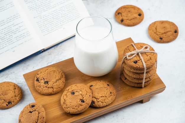 A glass cup of milk with chocolate cookies on a wooden cutting board.