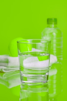 Glass cup of mineral water on green background