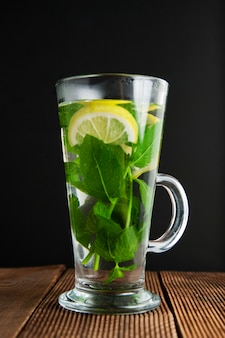 Glass cup of mint tea with lemon slices, dark background.