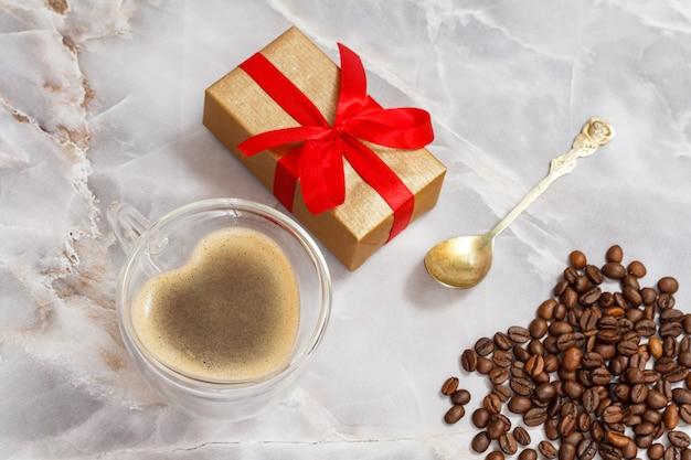 ガラスのコーヒーカップ、スプーン、ギフトボックス、ローストしたコーヒー豆をキッチンのテーブルに置きます。上面図。