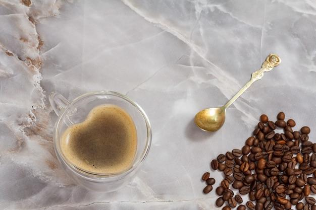ガラスのコーヒーカップ、スプーン、ローストしたコーヒー豆をキッチンのテーブルに置きます。上面図。