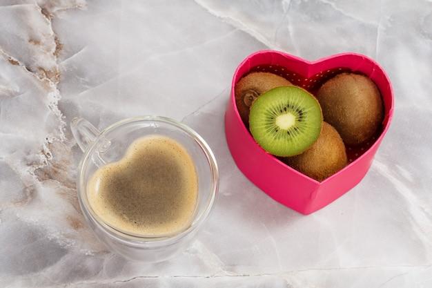台所のテーブルにコーヒーのガラスのカップとキウイフルーツのギフトボックス。コップ