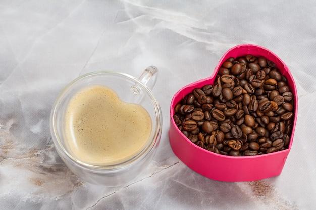 ガラスのコーヒーカップと、キッチンのテーブルにローストしたコーヒー豆が入ったギフトボックス。ハートの形をしたカップとボックス。上面図。