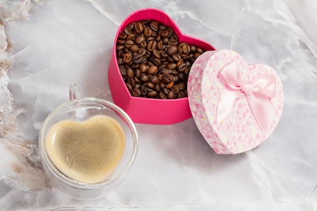 キッチンテーブルにコーヒーのガラスカップとローストコーヒー豆のギフトボックス
