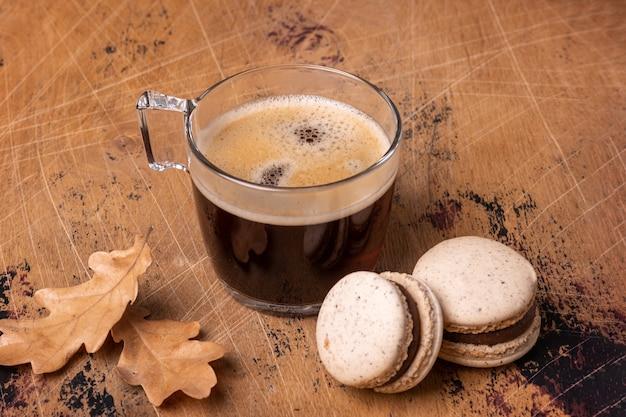 나무 배경에 커피와 초콜릿 마카롱의 유리 컵. 아늑한 가을 구성 - 이미지