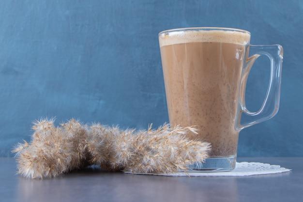 青い背景のパンパスグラスの隣のコースターにコーヒーラテのガラスカップ。高品質の写真