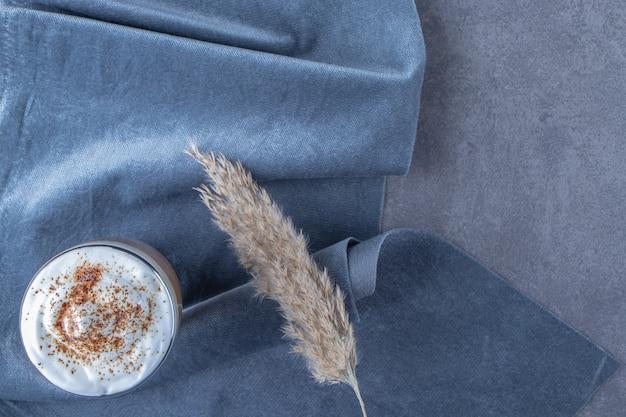 Стеклянная чашка латте кофе на куске ткани рядом с травой пампасов, на синем столе.