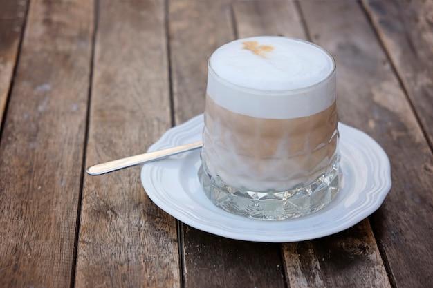 나무 테이블에 커피 라 떼의 유리 컵