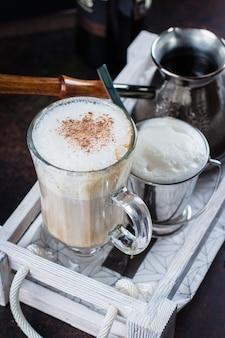 나무 쟁반에 커피 라 떼의 유리 컵