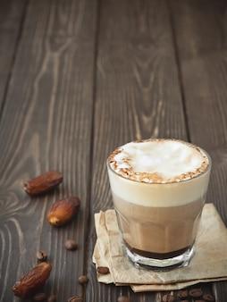 暗い木製の表面に牛乳とコーヒーのガラスのコップ