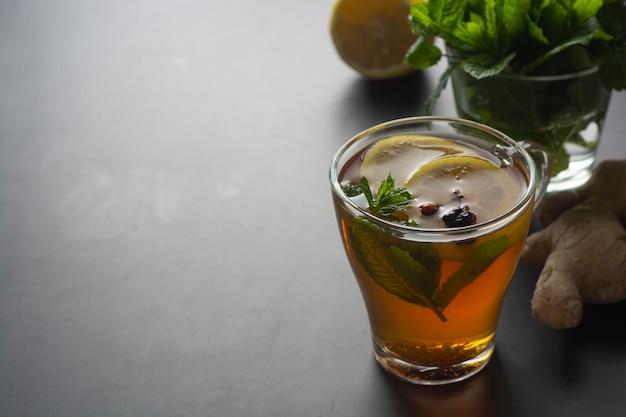 Стеклянная чашка имбирного чая с лимонами и листьями мяты на темной поверхности,
