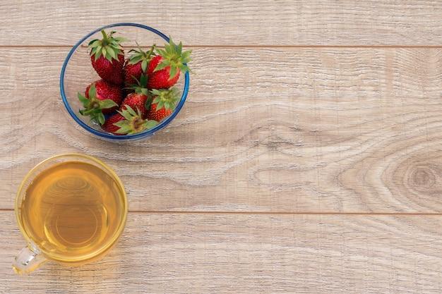 나무 배경에 신선한 딸기와 녹차와 유리 그릇의 유리 컵. 복사 공간이 있는 상위 뷰입니다.