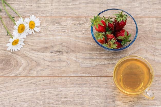 緑茶のガラスカップ、カモミールの花、木製の背景に新鮮なイチゴとガラスのボウル。コピースペースのある上面図。