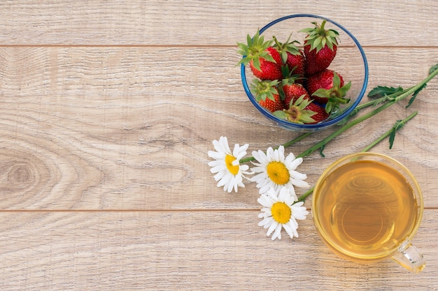 緑茶のガラスカップ、カモミールの花、木の板に新鮮なイチゴとガラスのボウル。上面図。