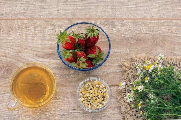緑茶のガラスカップ、カモミールの花、マトリカリアカモミールのドライフラワーと木製の背景に新鮮なイチゴとガラスのボウル。上面図。