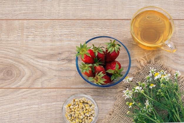 緑茶のガラスカップ、カモミールの花、マトリカリアカモミールのドライフラワーと木の板に新鮮なイチゴのガラスのボウル。上面図。