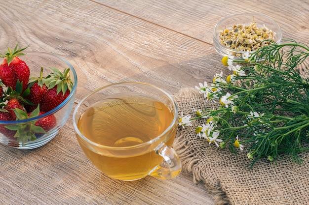 녹차 유리 컵, 자루천에 카모마일 꽃, 마트리카리아 카모밀라의 마른 꽃과 나무 판자에 신선한 딸기가 있는 유리 그릇.