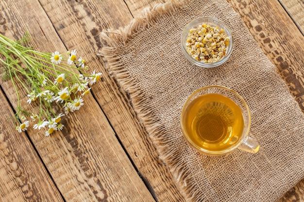 緑茶のガラスカップ、荒布にマトリカリアカモミールのドライフラワーと古い木の板に新鮮な白いカモミールの花が付いた小さなガラスのボウル。上面図。