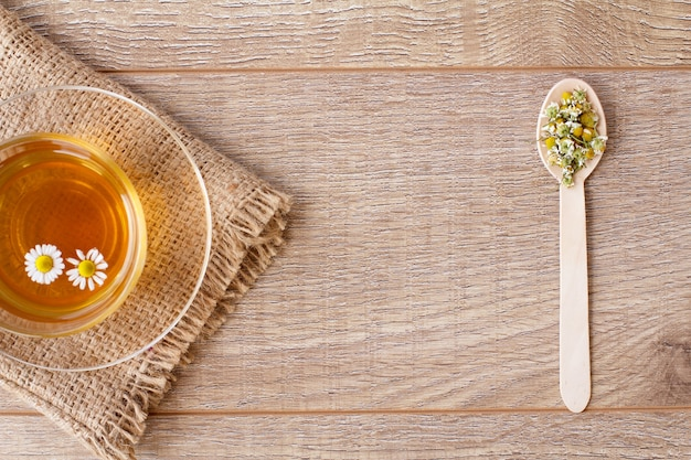 木製の背景にスプーンで乾燥カモミールの花と緑茶のガラスカップ。上面図