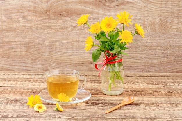 花瓶にカレンデュラの花とオレンジカレンデュラの新鮮な花束と緑茶のガラスカップ。木の板の背景。健康を与える飲み物。 Premium写真