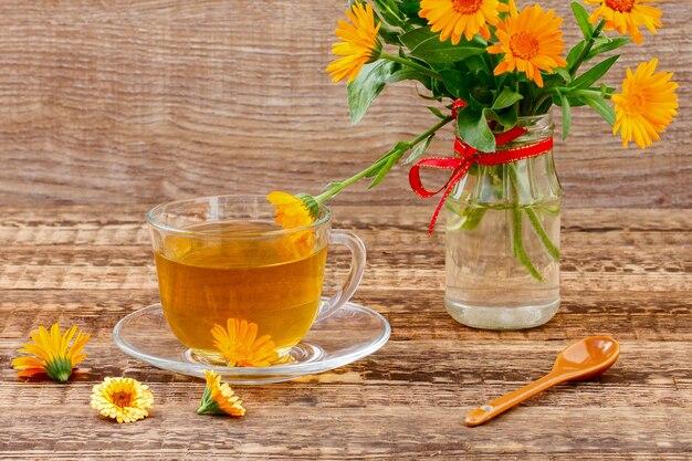 꽃병에 금송화 꽃과 오렌지 금송화의 신선한 꽃다발과 함께 녹차의 유리 컵. 나무 보드 배경입니다. 건강을 주는 음료.