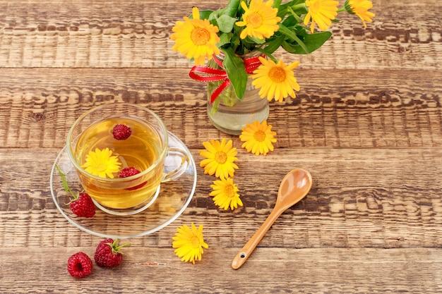 금송화 꽃과 신선한 산딸기, 꽃병에 오렌지 금송화의 신선한 꽃다발과 함께 녹차의 유리 컵. 나무 보드 배경입니다. 건강을 주는 음료.