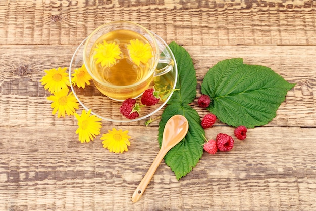 나무 배경에 금송화와 신선한 라즈베리의 꽃과 함께 녹차의 유리 컵. 건강을 주는 음료.