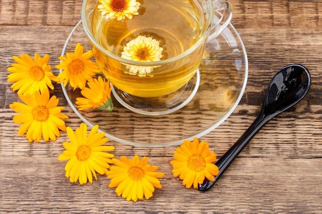 나무 배경에 금송화 꽃과 함께 녹차의 유리 컵. 건강을 주는 음료.