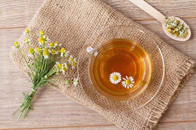 白いカモミールの花と木製の背景にバッグと緑茶のガラスカップ。上面図