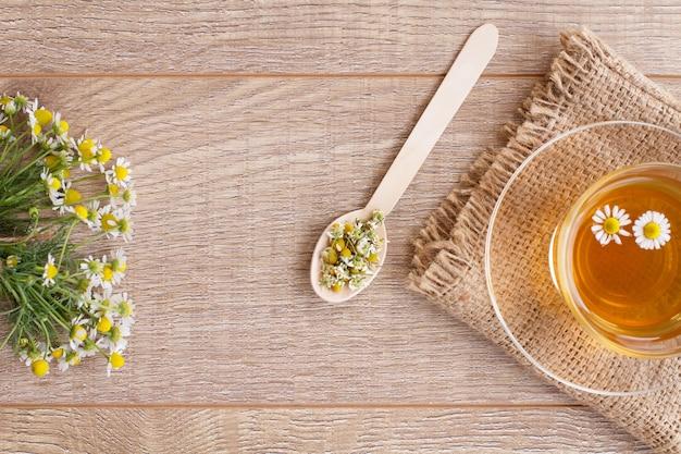 木製の背景に白いカモミールの花と緑茶のガラスカップ。上面図