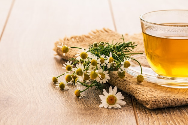 木製の背景に白いカモミールの花と緑茶のガラスカップ