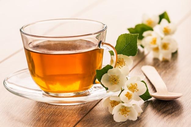 白いジャスミンの花と木製の背景にスプーンと緑茶のガラスカップ