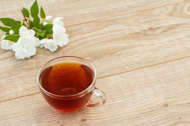Стеклянная чашка зеленого чая с белыми цветами жасмина на деревянных фоне. вид сверху с копией с интервалом.