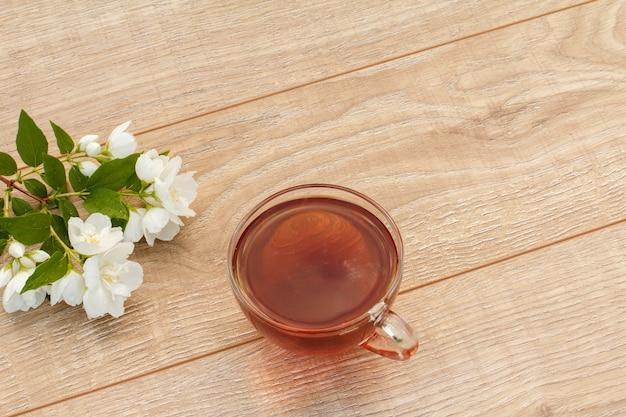 Стеклянная чашка зеленого чая с белыми цветами жасмина на деревянных фоне. вид сверху.
