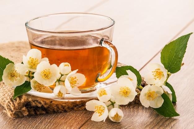 木製の背景に白いジャスミンの花と緑茶のガラスカップ