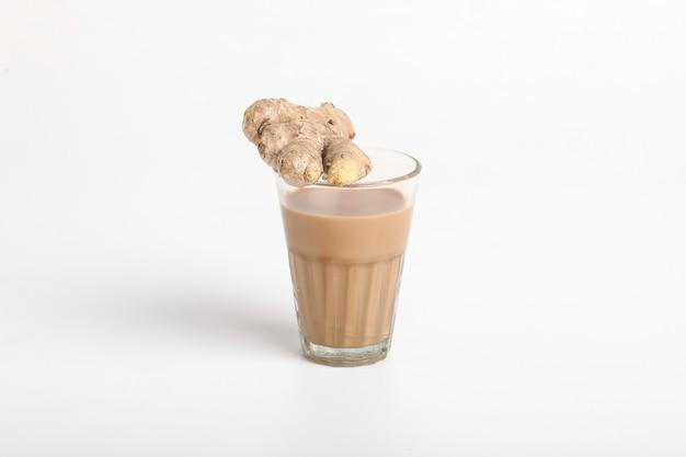 白い表面に分離された生姜の根茎をスライスしたホットジンジャーティーのガラスカップ