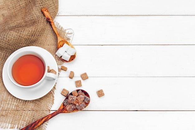 Стеклянная чашка горячего чая с сахаром на фоне стола