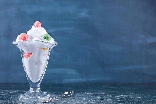 Стеклянная чашка для мороженого, украшенная конфетами на мраморе.
