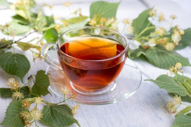 Стеклянная чашка липового чая и цветы липы на белом деревянном столе. горячий напиток здравоохранения.