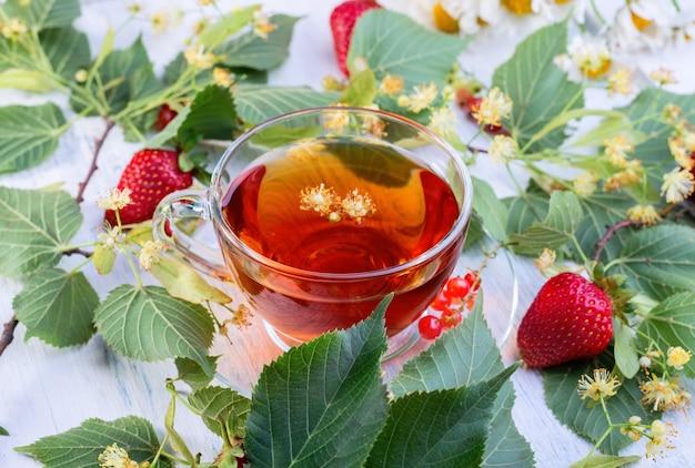 Стеклянная чашка липового чая с липовыми цветами, листьями и клубникой на старом белом деревянном столе. горячий напиток здравоохранения.