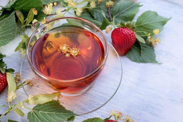 린든 꽃, 잎 및 오래 된 흰색 나무 테이블 상단보기에 딸기와 린든 차 유리 컵. 건강 관리 뜨거운 음료.