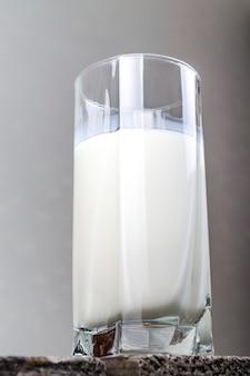 木製のテーブルの上の牛乳のガラスカップ