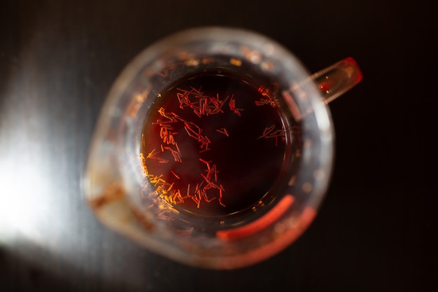 木製のテーブルにルイボスティーのガラスカップ。